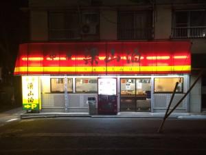 駐車場から見た外観。暗い青梅街道に赤と黄色の看板が光ります。