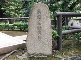 像の傍らに立つ石碑。